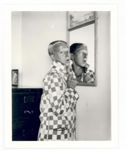 Self-portrait (reflected image in mirror, checqued jacket) by Claude Cahun, 1928. Jersey Heritage Collections (c) Jersey Heritage